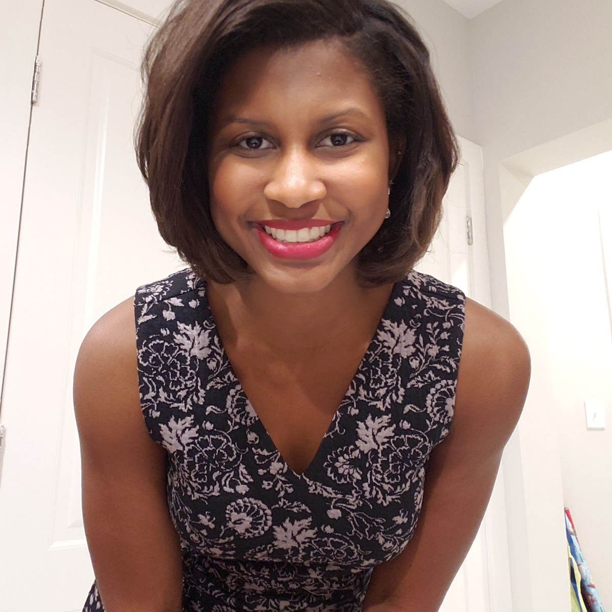 Jalynn smiling with red lipstick, short haircut, and happy