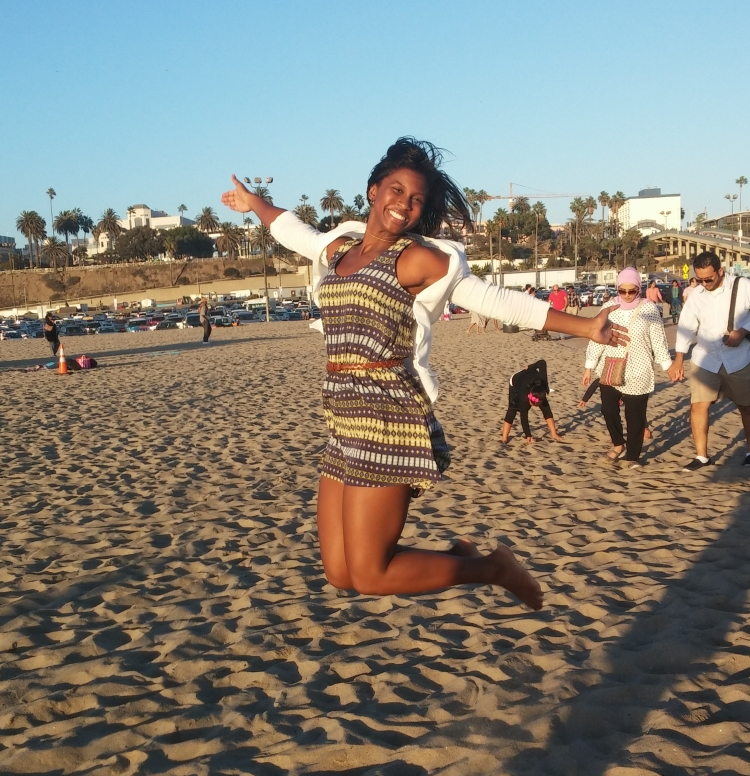 girl jumping and smiling in the sunshine and sand at the beach
