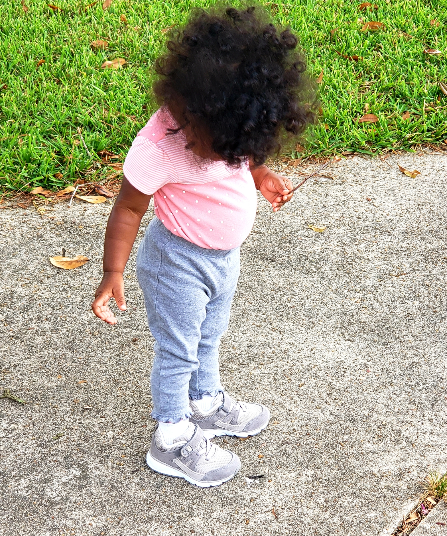 toddler girl with curly hair looking at her shoes